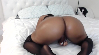 Black woman with big ass fucks herself with a dildo in front of a webcam