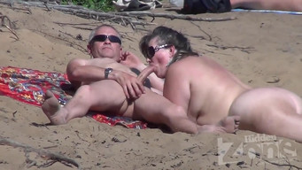 Wife pleases her husband with a public blowjob on a nudist beach