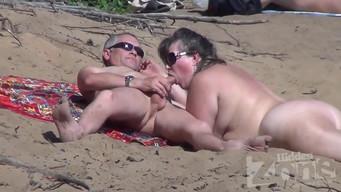 Filming a blowjob performed by a mature nudist on the beach