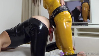 Mistress in yellow latex hammering a slave's ass and sucking cum from a dick